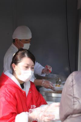 7丁目エバラ食品1万人振る舞い鍋、手前お客様に振舞う、吉田くん。奥、調理&給仕するコックコート姿のくま社長